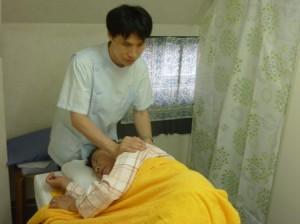 患者さんが横向きに寝て、肩をマッサージしている写真