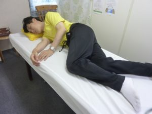 横向きで寝、上側の足を前側にしベッドについている写真