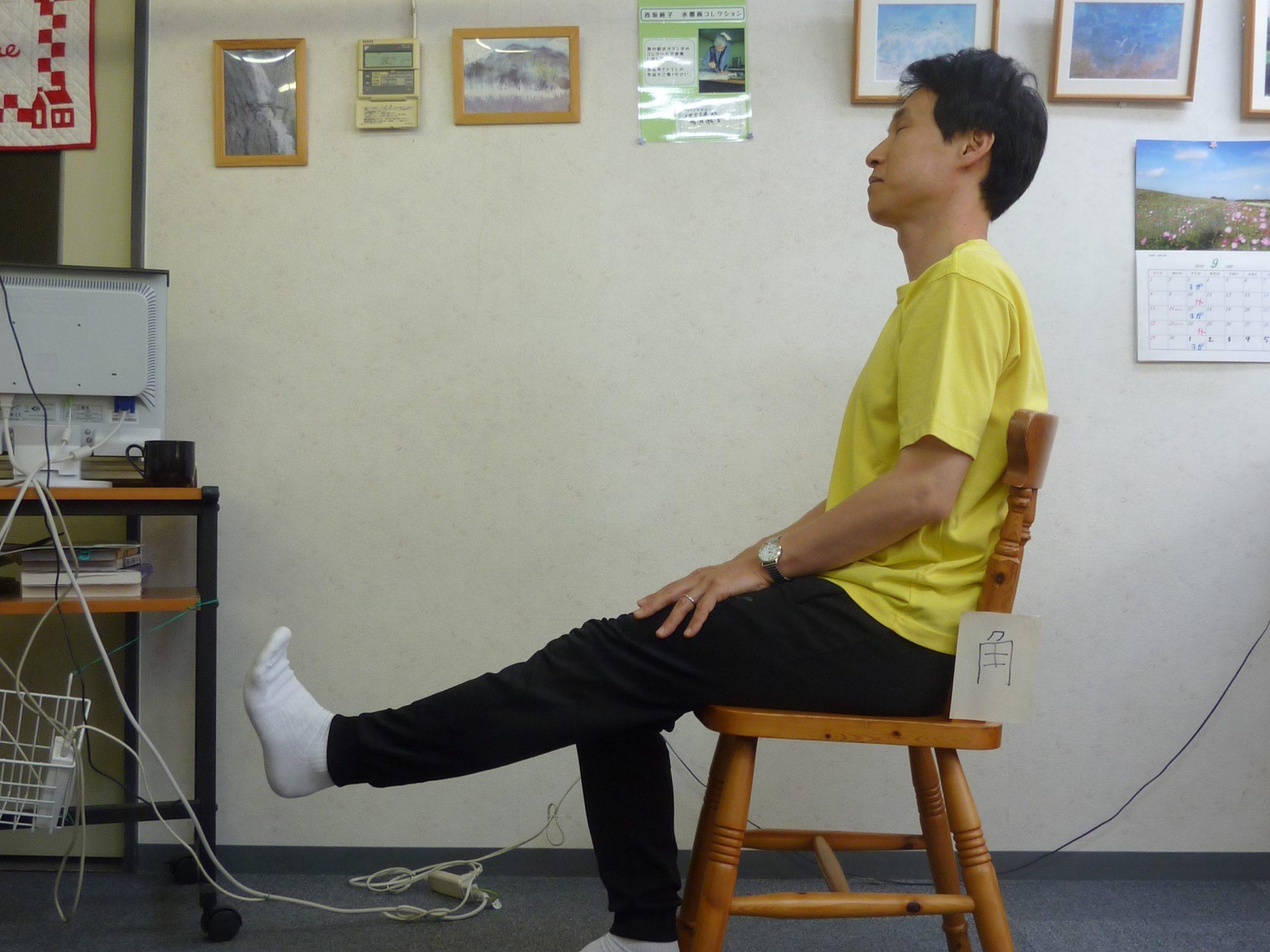 椅子に座った人がひざ下を伸ばすエクササイズをしています
