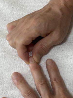 中指を指圧している写真