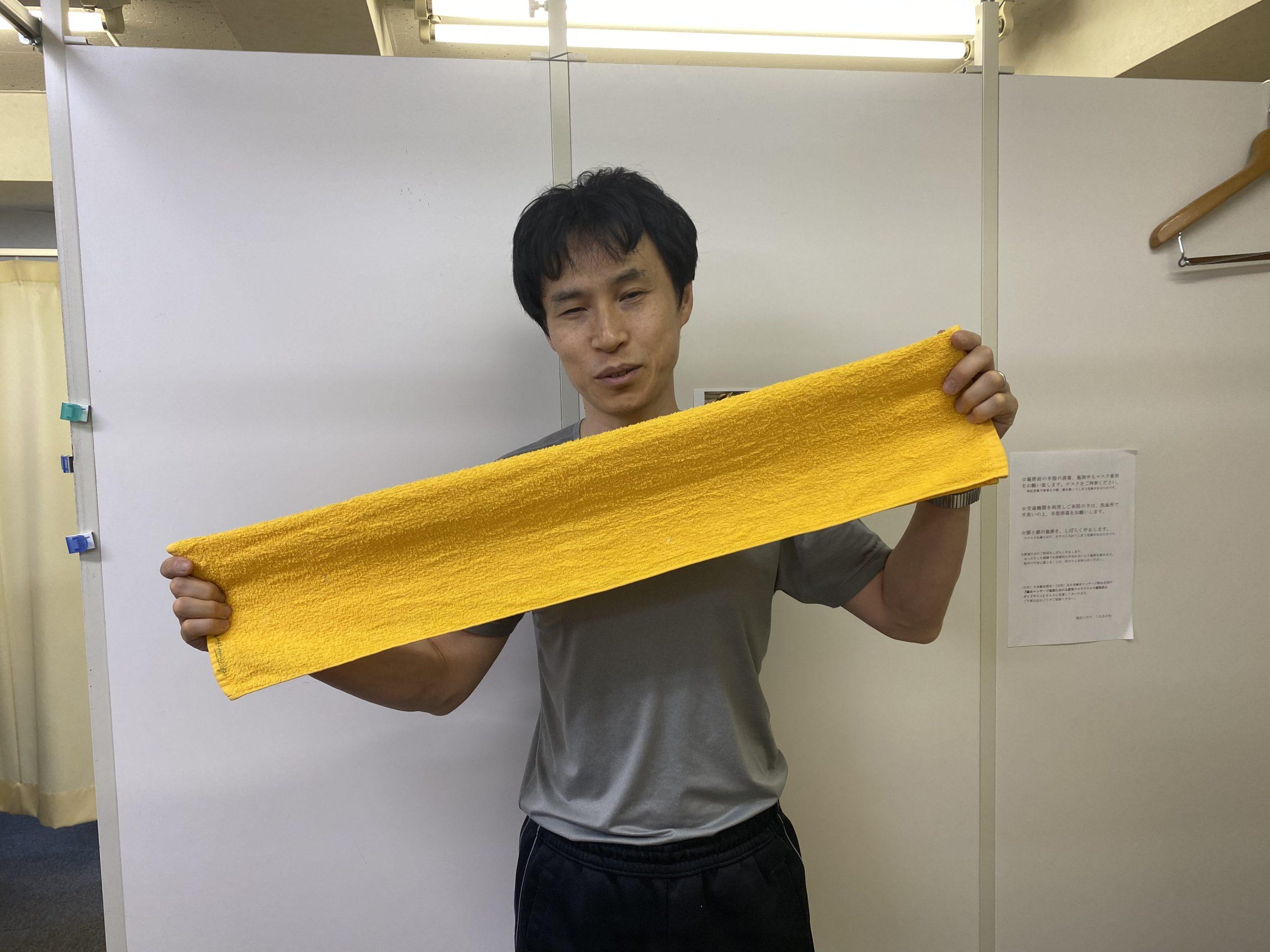 タオルを細長い二つ折りにして持っている写真